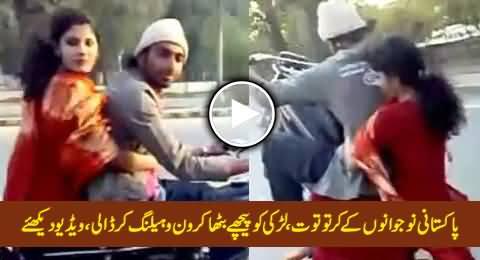 Pakistani Boy Performing One Wheeling with A Girl Sitting on Bike
